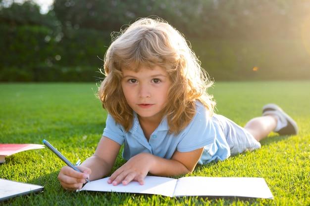 子供の外のノートに鉛筆で書いているかわいい素敵な子供は、公園の夏休みの家で本を読みます...