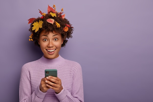 かわいい素敵な暗い肌の女の子は、現代の携帯電話を保持し、カメラを直接見て、電話をかけ、幸せに笑い、カジュアルな服を着て、秋の間にポーズをとり、紫色の壁に隔離されています