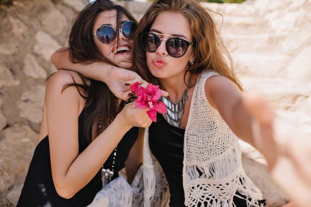 トレンディなネックレスとニットの服装でかわいい素敵な女の子がピンクの花を抱いて笑っている友人を抱きしめます。夏休みに外をぶらつくスタイリッシュなサングラスをかけた2人の素晴らしい姉妹