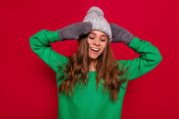 Cute lovely happy woman with long hair dressed winter cap and green sweater  standing over red background with closed eyes, happy smile and calm emotions