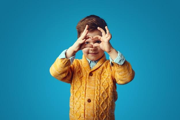 Милый милый ребенок в желтом кардигане показывает форму сердца руками