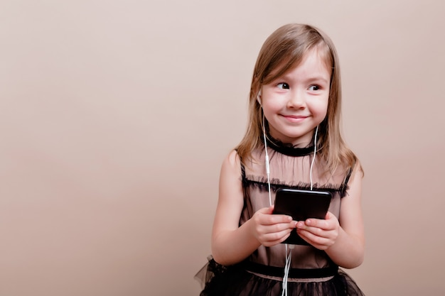 ヘッドフォンで音楽を聴き、大きな感情で孤立した壁にポーズをとって、魅力的な笑顔でかわいい素敵な女の子、テキストの場所
