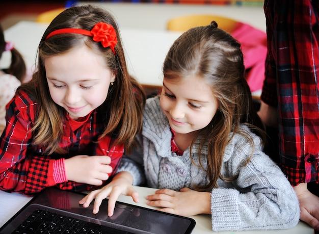 かわいい素敵な学校の子供たちが教育活動をしている教室