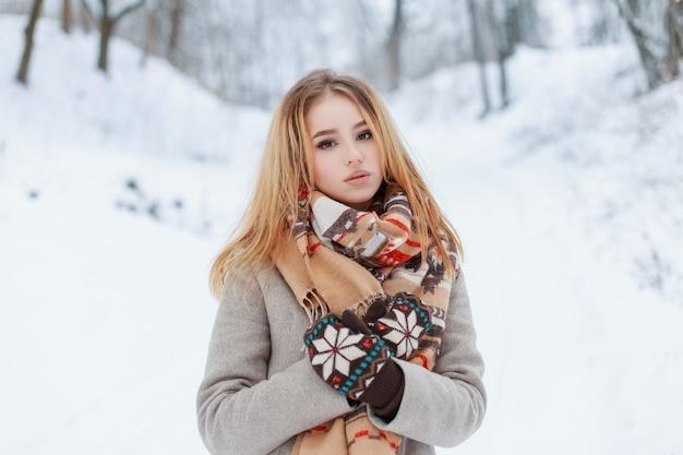 겨울 추운 날에 자연 속에서 쉬고있는 멀티 컬러 패턴이있는 모직 베이지 스카프가있는 모직 빈티지 장갑의 세련된 겨울 코트에 귀여운 사랑스러운 젊은 여성. 세련된 소녀.