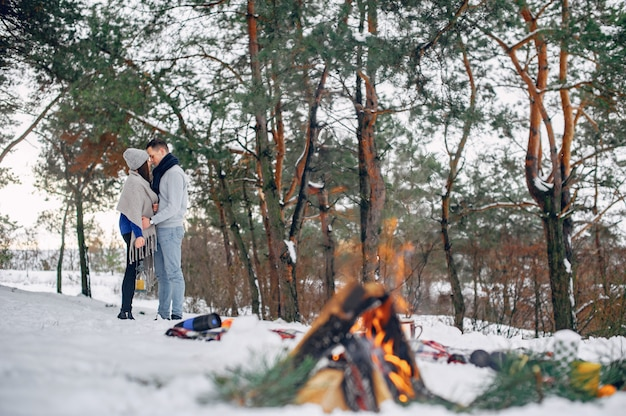 Cute and loving couple in a winter forest