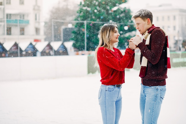 Cute and loving couplein a red sweaters in a winter city