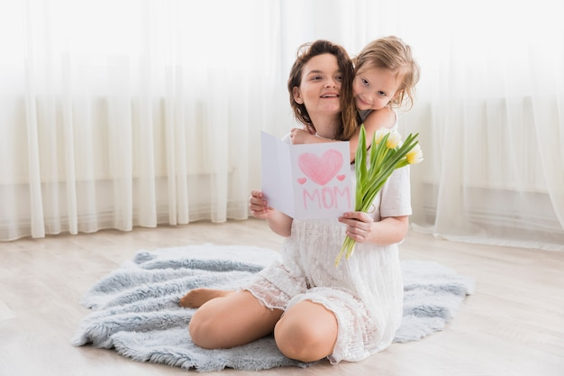 Cute loving mother and daughter at home with holding greeting card and tulip flowers