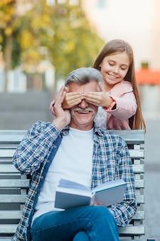 かわいいlsmilingittle女の子はベンチで祖父と一緒に時間を過ごします