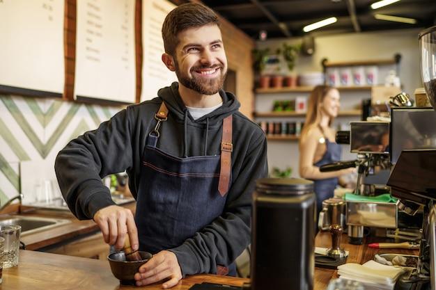 Симпатичная мужская бариста положила в кофе эспрессо переносной фильтр для приготовления кофе