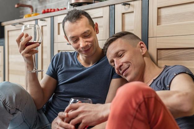 かわいい男性の同性愛者のカップルは一緒に時間を過ごします。彼らは台所の床に座ってワインを飲みます