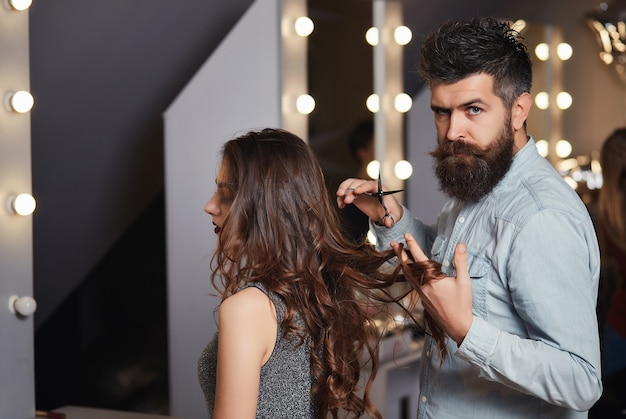 Cute male hairdresser makes haircut a young woman in a beauty salon.