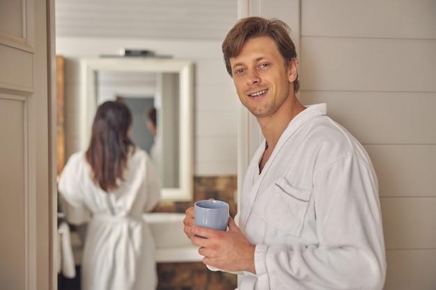 흰색 부드러운 목욕 가운 포즈와 사진 카메라를보고 귀여운 남성