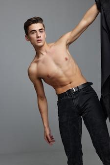 Симпатичный мужчина в черных штанах и гламурная модная студия серая модель образа жизни