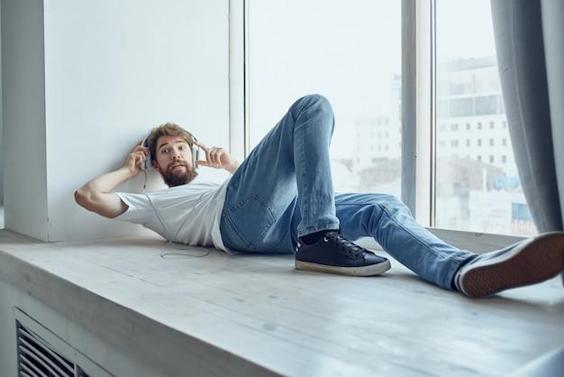 楽しいヘッドフォンを身に着けている窓の近くに横たわっているかわいい男