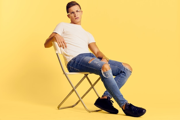 Cute man sitting on a chair white t-shirt jeans lifestyle modern style