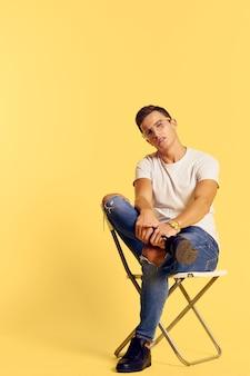 椅子に座っているかわいい男白いtシャツジーンズ