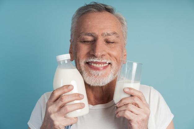 회색 머리와 수염을 가진 귀여운 남자는 닫힌 눈으로 웃고, 우유 병과 유리를 보유하고 있습니다.