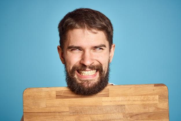 顔の近くにキッチンボードを持つかわいい男、笑顔