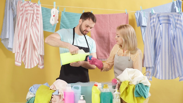 Cute married couple chose a detergent for washing dirty clothes with spots and stains