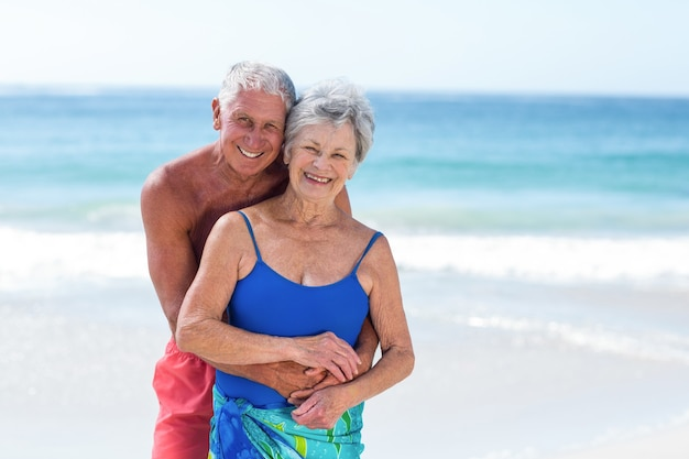 Симпатичная зрелая пара обнимается на пляже