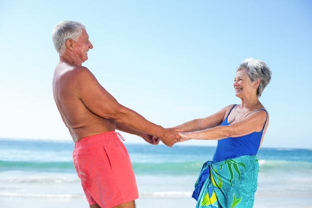 Милая зрелая пара, взявшись за руки на пляже