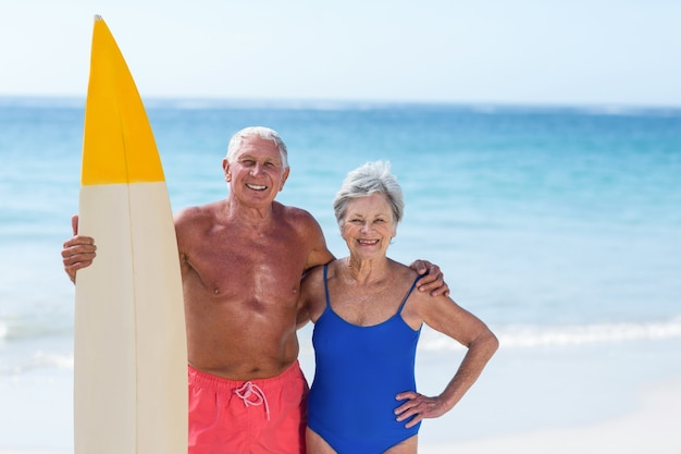 Cute mature couple holding a surfboard