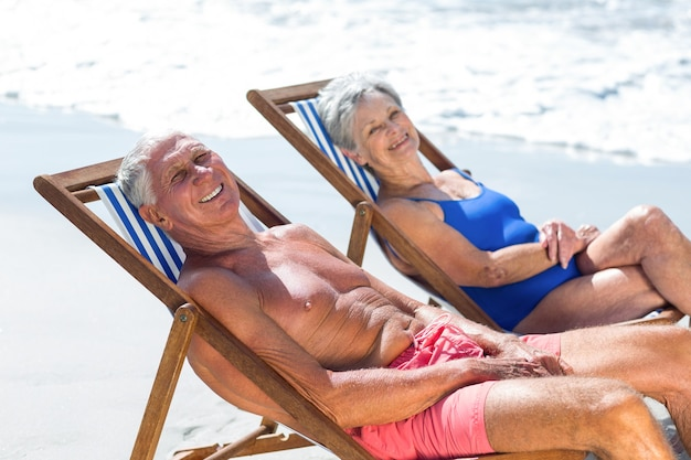 Cute mature couple lying on deckchairs