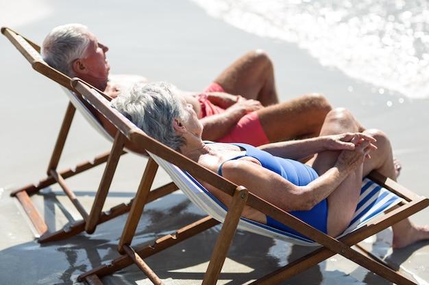 Милая зрелая пара, лежа на шезлонгах