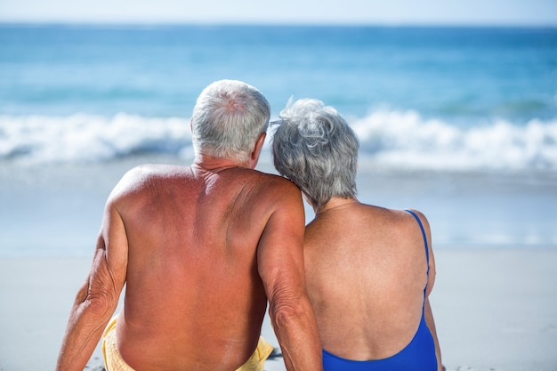 Cute mature couple sitting on the beach looking at the sea
