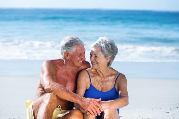 Cute mature couple sitting on the beach
