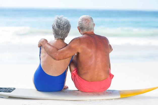 Милая зрелая пара, сидящая на доске для серфинга