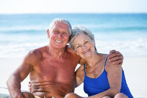 Милая зрелая пара сидит на пляже