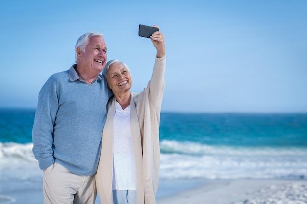 Cute mature couple taking selfie on the beach