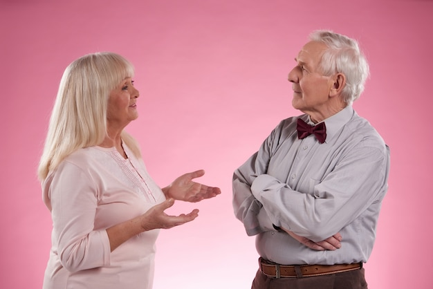 Cute mature woman tells something to old man in bow tie.