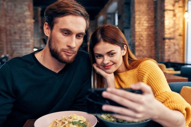 그들의 손에 휴대 전화와 함께 레스토랑에서 귀여운 남녀 셀카