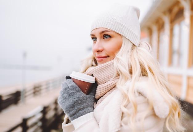 かわいい中年のブロンドの女性は、冬の日に屋外で時間を楽しんでいます。薄手のジャケット、帽子、スカーフを身に着け、温かい飲み物を飲む女性。