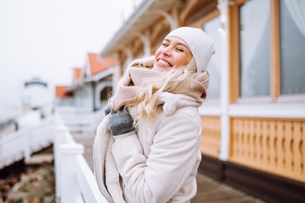 Cute middle-aged girl enjoy time outdoor at winter day. female wear light jacket, hat, scarf and laughing.