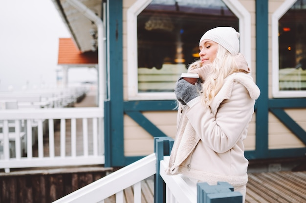 Cute middle-aged woman enjoy time outdoor at winter day. female wearing a light jacket, hat, scarf and drink hot beverage.