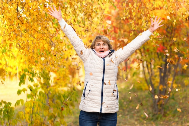 Cute middle-aged woman in nature in autumn. mature woman walking in the park, she is happy. she held up her hands.