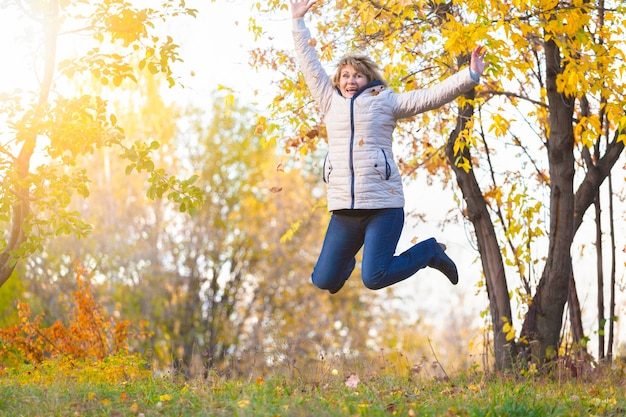 Cute middle-aged woman in nature in autumn. mature woman walking in the park, she is happy. she jumps.