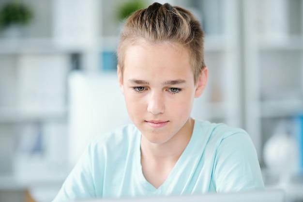 Симпатичный мальчик средней школы, концентрирующийся на индивидуальной работе, глядя на дисплей беспроводной технологии
