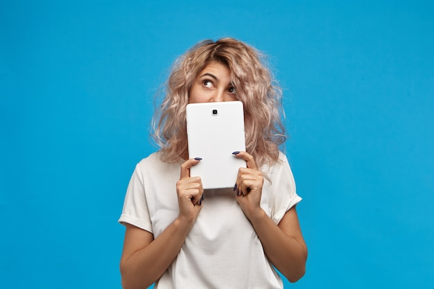 곱슬 분홍빛이 도는 머리를 가진 귀여운 천년 젊은 여성, 생각하는 표정, 찾고, 그녀의 얼굴에 디지털 태블릿을 들고. 현대 기술