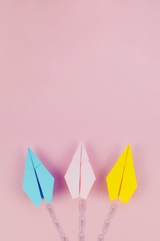Cute minimalist paper planes with trail on pink background