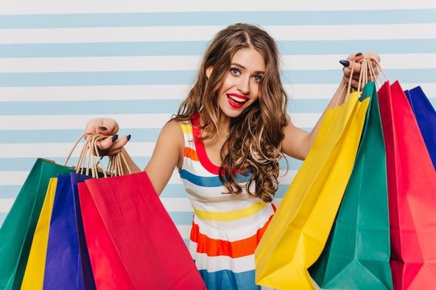 곱슬 검은 머리와 아름다운 핑크 립스틱 포즈를 취하는 귀엽고 장난 꾸러기 소녀. 흰색과 파란색 벽에 새 옷으로 가득한 패키지로 쇼핑을 사랑하는 여자의 초상화