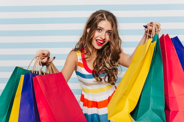 Cute, mischievous girl with curly dark hair and beautiful pink lipstick posing. portrait of woman loving shopping with packages full of new clothes in white and blue wall