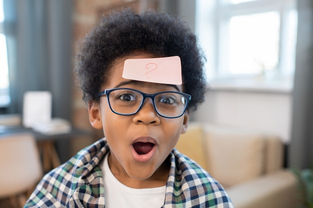 Cute mixed-race boy with notepaper with question mark on his forehead looking at you while standing in front of camera in home environment