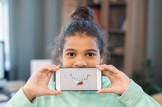 Cute mixed-race girl in casualwear holding smartphone with funny smile and tongue on screen in front of her mouth against home environment