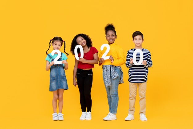 Cute mixed race kids smiling and holding 2020 numbers