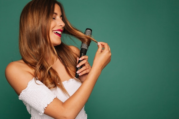 Cute model laughing with hair curler