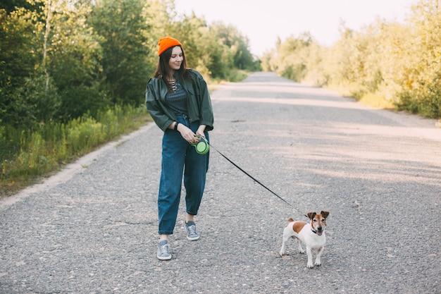 Симпатичная современная девушка в зеленой куртке и оранжевой шляпе гуляет с собакой в природе.